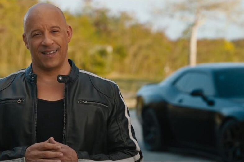 Vin Diesel, having driving a muscle car out to the middle of nowhere, addresses a camera
